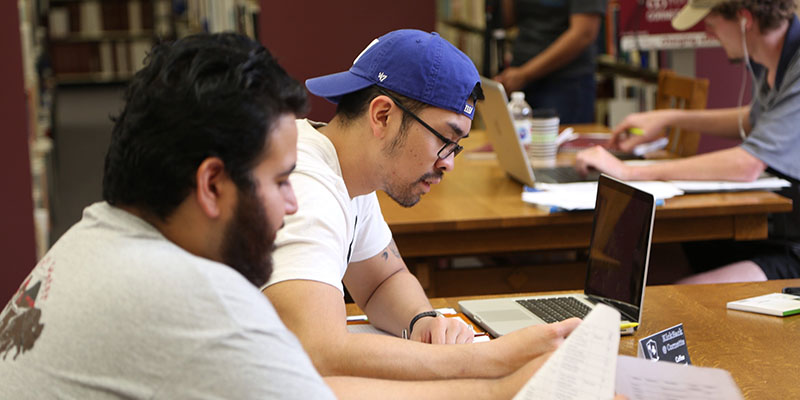 two male students working on assignments in the library