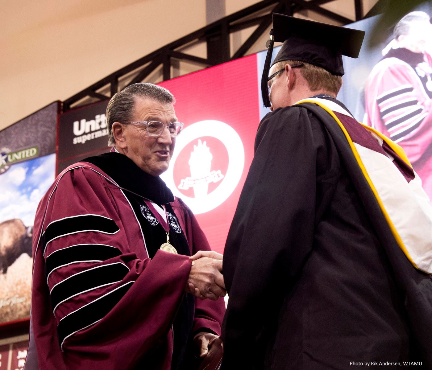President Wendler shaking hand of graduate at commencement