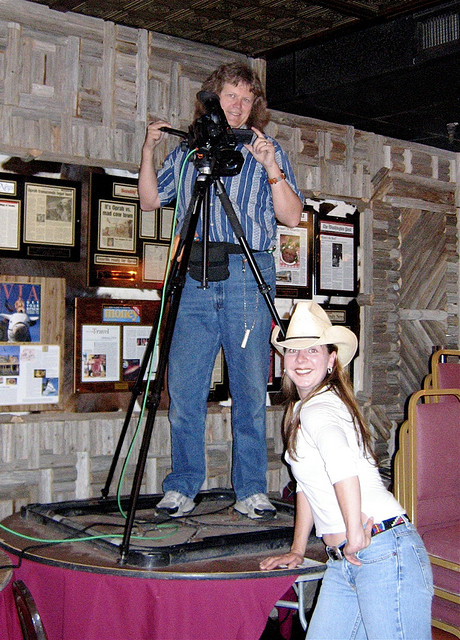 Woman in cowboy hat stands next to videographer with camera