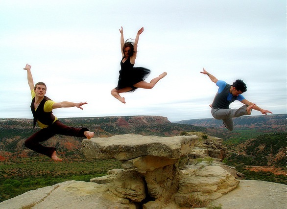 Three dancers leaping off the ground in a canyon.