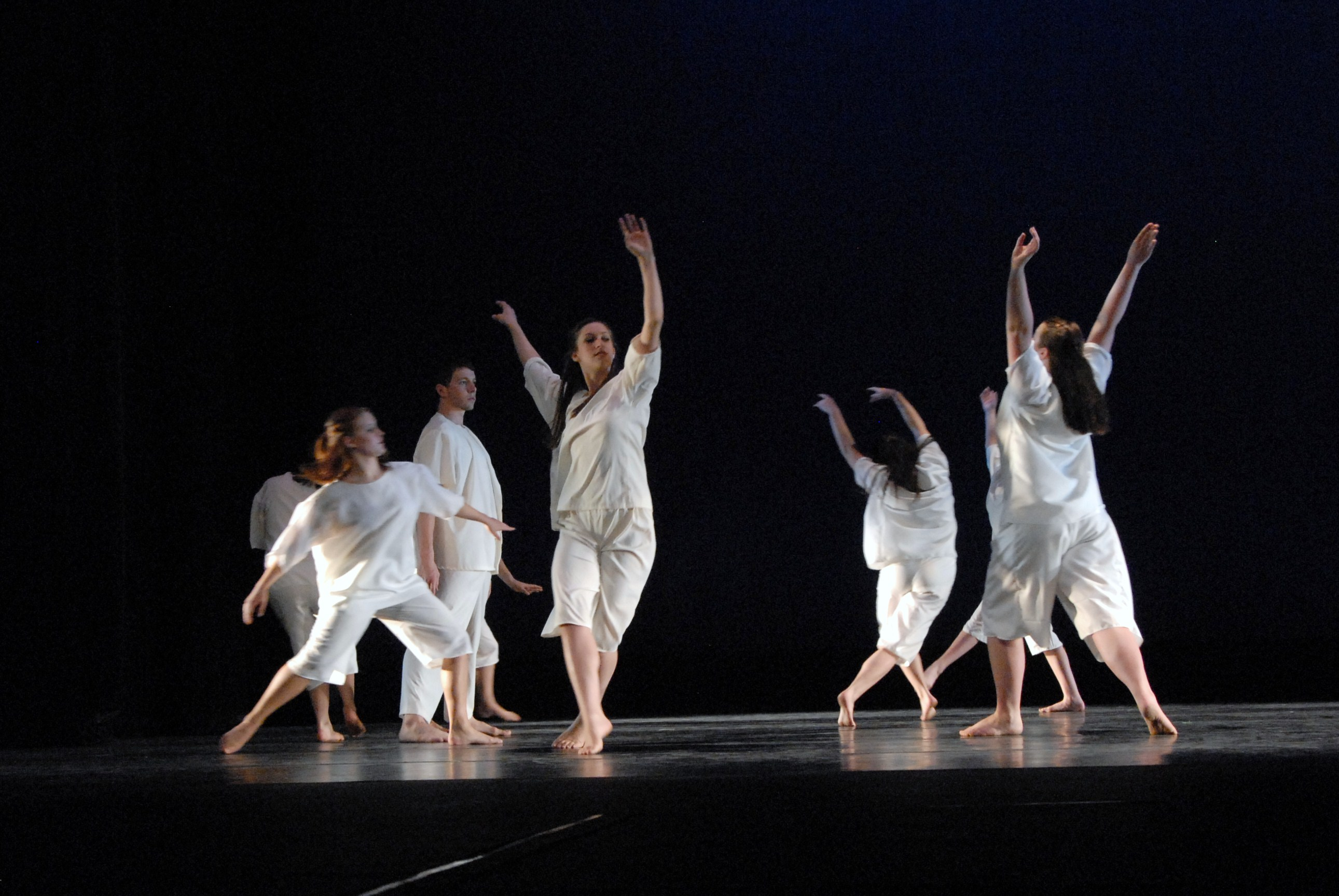 Multiple dancers on stage in white