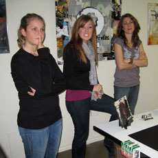 Three female students standing in an art classroom.