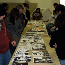 Students standing around a table of art work during critique.