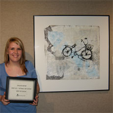 Student stands next to her framed artwork with an award.